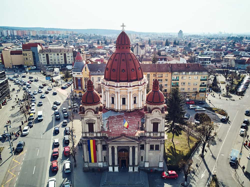 Aerial shot of Targu Mures old city with town hall and church on background at daylight. Traffic jam. Romania