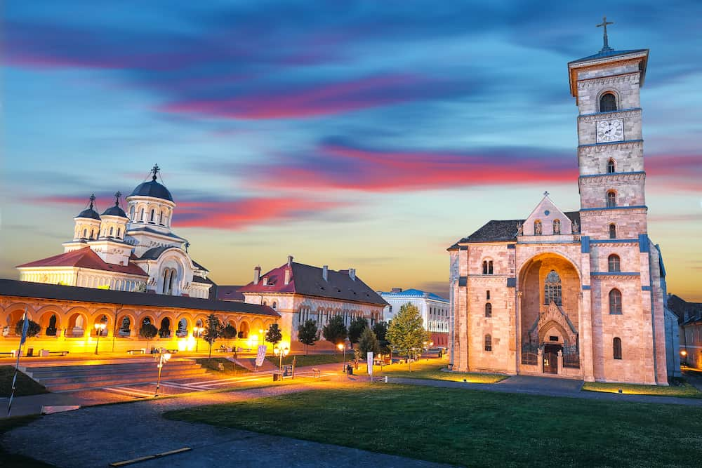 The Coronation Orthodox Cathedral and Roman Catholic cathedral in Fortress of Alba Iulia. Dramatic evening summer scene of Transylvania, Alba Iulia city, Romania, Europe