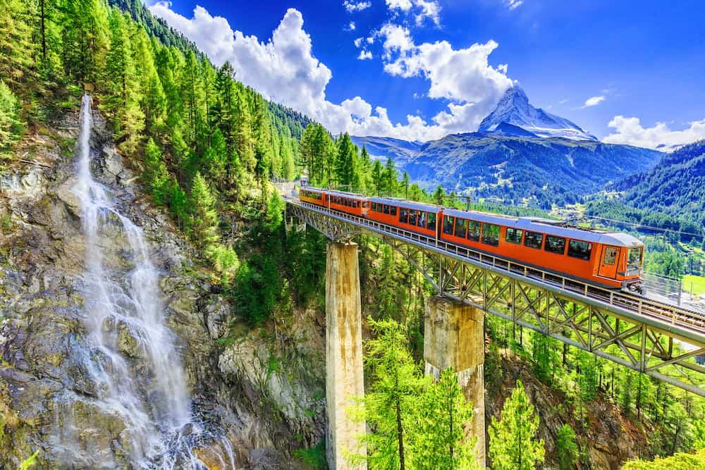 Zermatt Switzerland. Gornergrat tourist train with waterfall bridge and Matterhorn. Valais region.