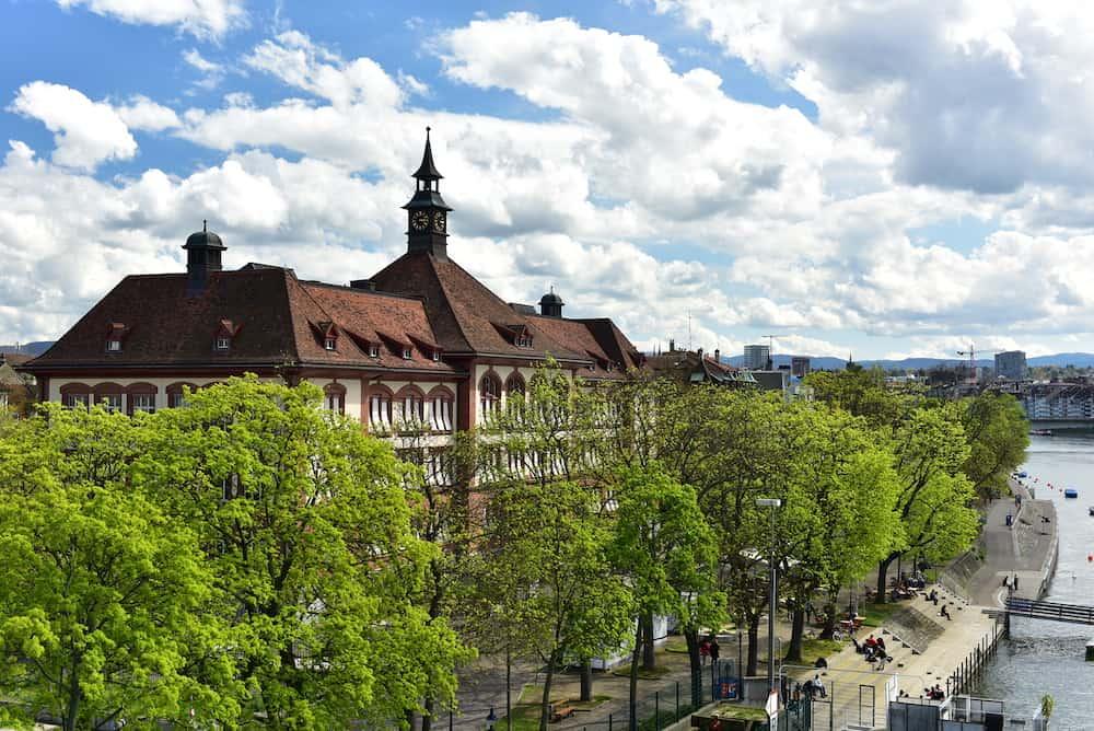 BASEL, SWITZERLAND - Embankment of the Rhine river. View of the Theobald Baerwart Secondary School. City of Basel, Switzerland, Europe