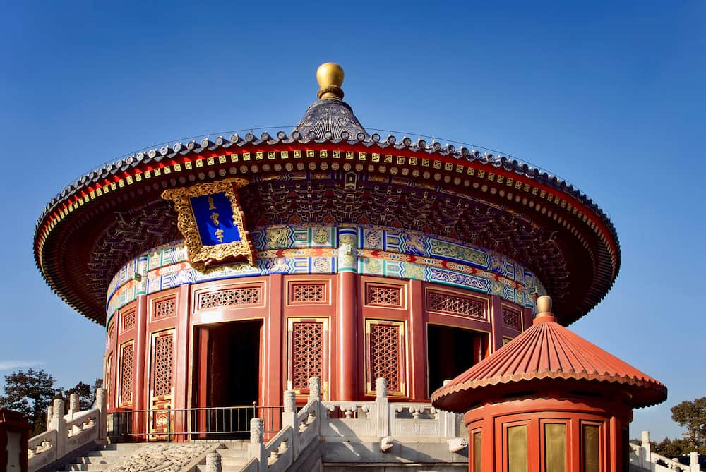 """Chinese ancient Temple of Heaven. Translation: """"Imperial Temple of Heaven"""". Asian architectural background. unique round roof of the temple on the blue sky background, Beijing. UNESCO World Heritage Site"""