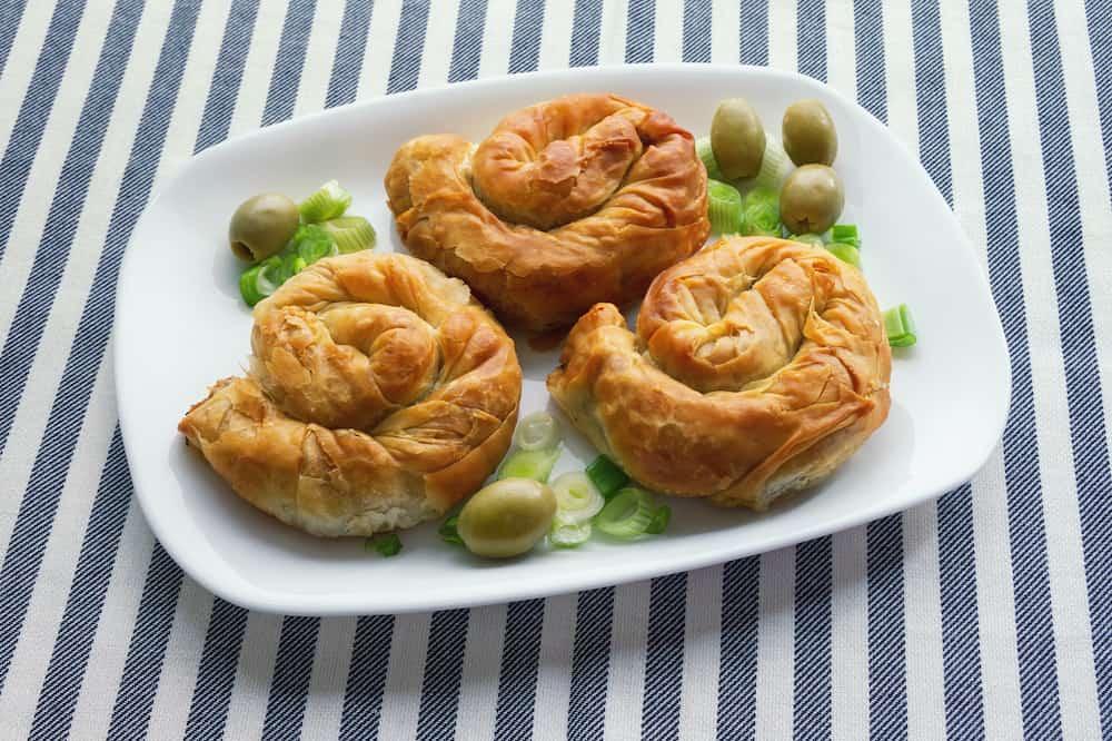 Balkan cuisine. Burek, baked filled pastries - popular national dish. Three round bureks on a white plate