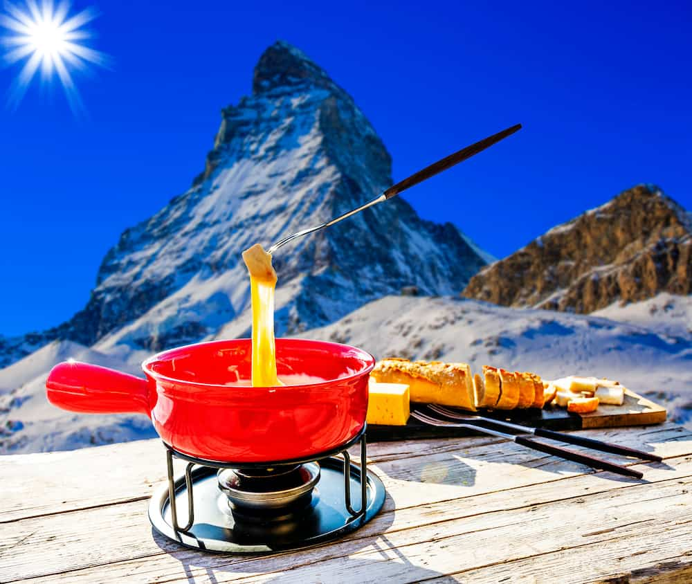 Fondue cheese, swiss winter ski holidays break for lunch, mountain view Matterhorn in Zermatt, Switzerland.