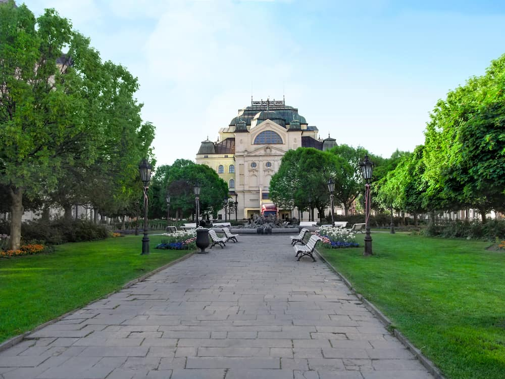 Kosice, Slovakia - Green spring park from the back of the Kosice State Theatre. Young grass, flowers, vintage street lamps and benches along alley against backdrop of theater building