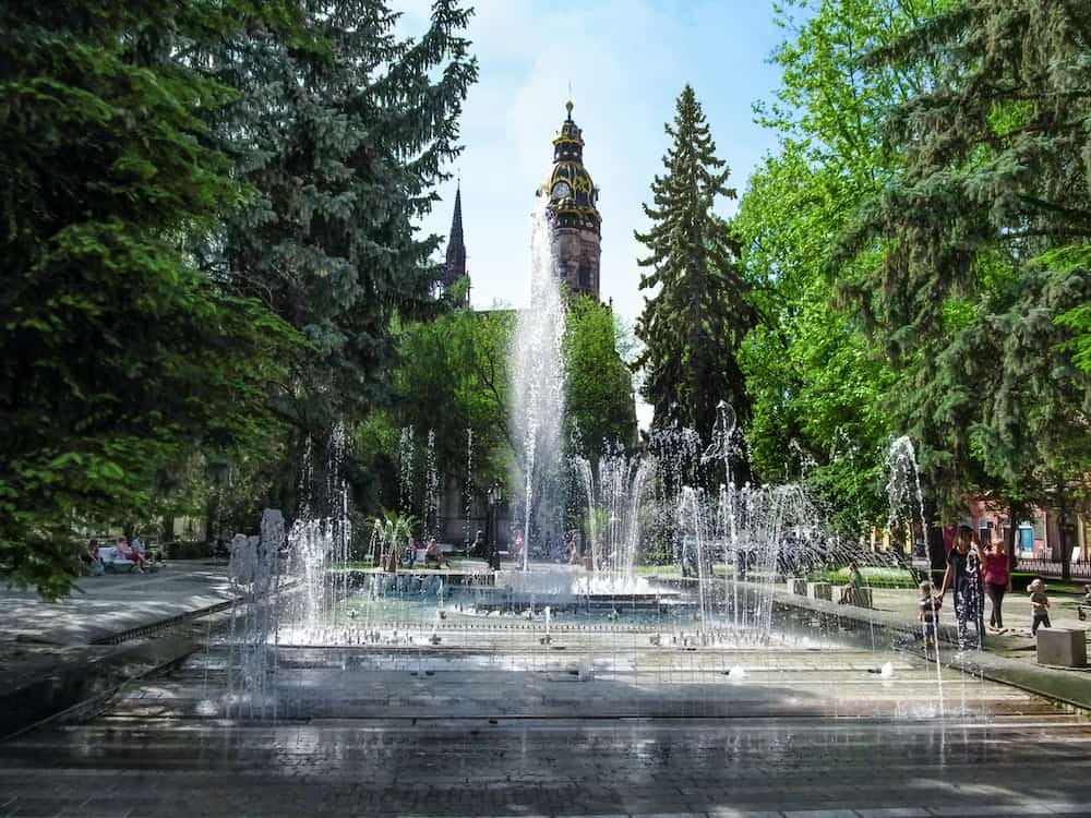 Kosice, Slovakia - Jets of water in fountain on background of Cathedral of St. Elizabeth in Kosice Park on a sunny spring day. Cityscape of modern park and tower of ancient Gothic temple