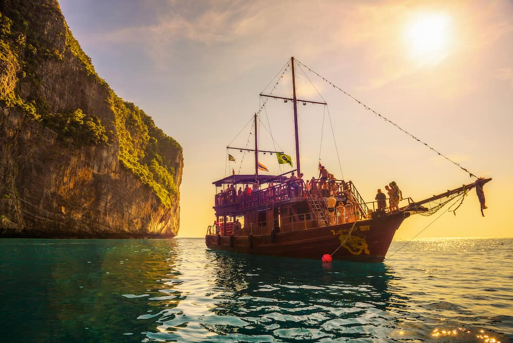 Koh Phi Phi Lee, Thailand A big boat in pirate style with many tourists enjoy a sunset at Maya Bay on Phi Phi island.