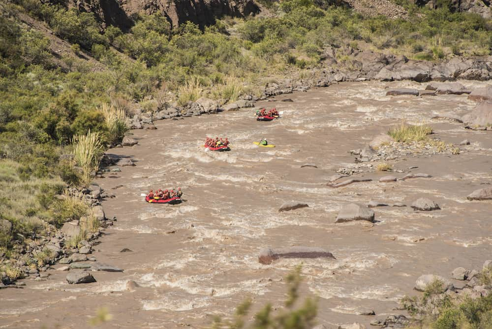 Rafting with three red rubber boats in the rushing waters of thaw in the andes