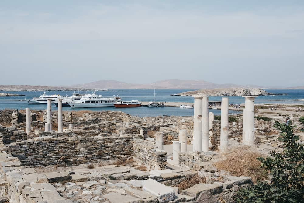 Delos, Greece - Ruins on the Island of Delos, archaeological site near Mykonos in the Aegean Sea Cyclades archipelago, tour boats docked on the background. Selective focus.