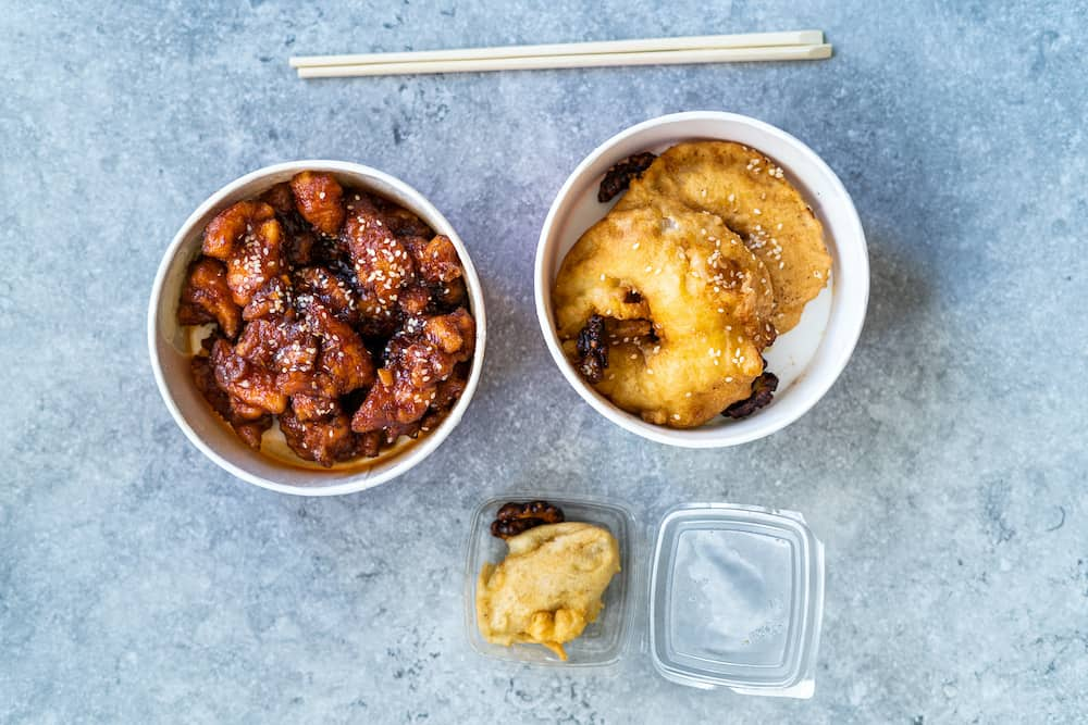 Take Away Asian Food Chinese General Tsos Chicken, Fried Pineapple Fritters Caramelized with Cinnamon and Sesame Seeds and Banana Wrapped with Crepe in Plastic Box Package / Container. Traditional Food.