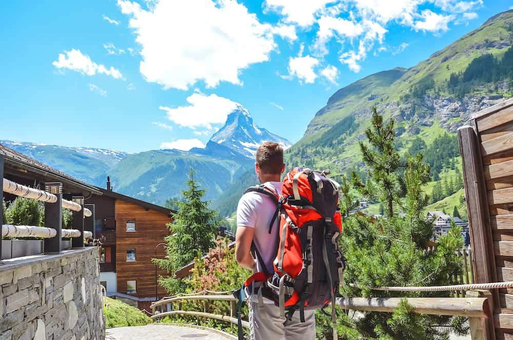 Caucasian man hiking in beautiful Zermatt, Switzerland. Matterhorn in background. Backpacking lifestyle, Millennials concept. Adventure, outdoor. Summer in Alps