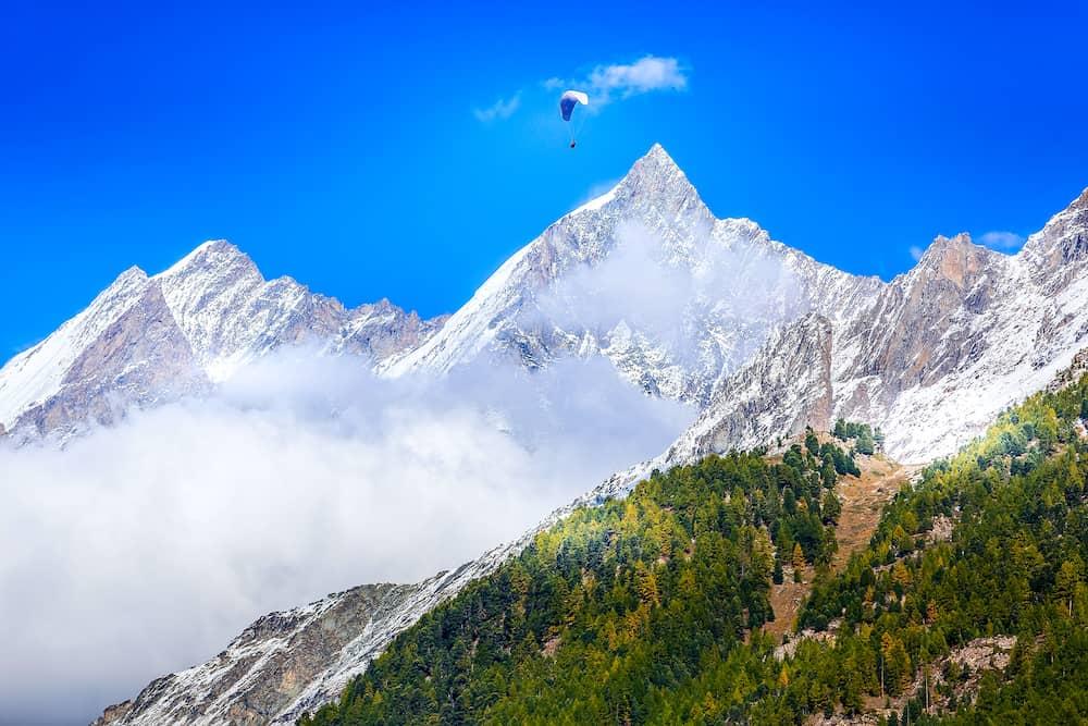 Paraglider over mountain snow peak, Swiss Alps, Zermatt, Switzerland