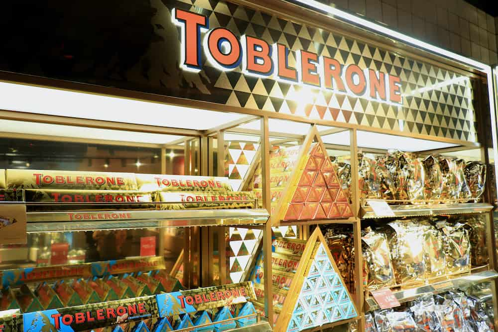 Amsterdam Schiphol Airport, the Netherlands : Toblerone chocolate, promotional display in airport shopping area. Various colors representing different flavors.