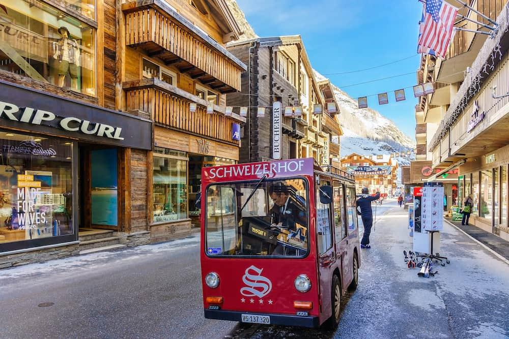 ZERMATT, SWITZERLAND - : Unidentified man drives electric delivery car by the main street of Zermatt, Switzerland. Zermatt is a combustion-engine car-free zone.