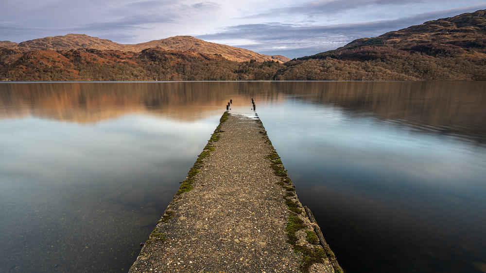 A long exposure of an old jetty on the shore of Loch Lomond, Scotland. Looking over to Inversnaid and the mountains of Loch Lomond National Park.