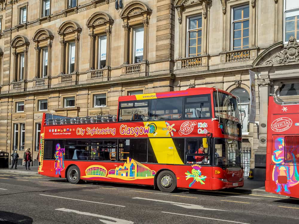 GLASGOW, SCOTLAND - City sightseeing tour bus in George's Square on July 20, 2017 in Glasgow, Scotland. Tour buses are a popular way for travellers to visit the city of Glasgow.
