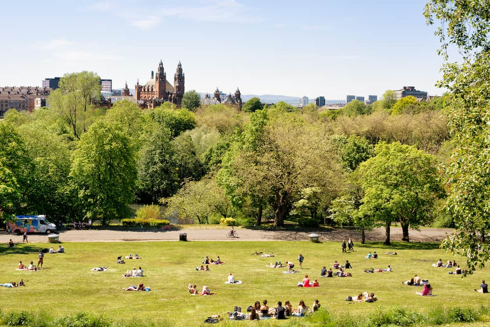 Glasgow Scotland UK: -Young people, students of the University of Glasgow enjoying a warm sunny day on the lawns of Kelvingrove park, Kelvingrove Art Gallery and Museum in the background