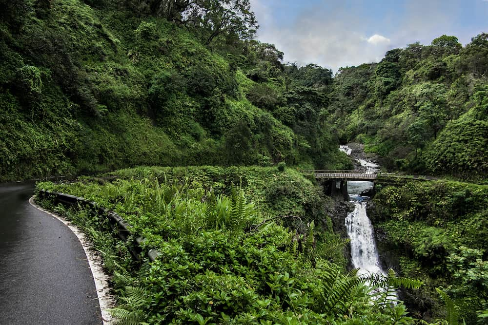 Road to Hana: The Hana Highway turns to cross a one lane bridge beside a waterfall on the north coast of Maui.