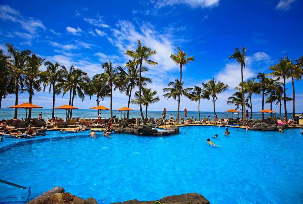The swimming pool at the Sheraton Waikiki hotel sits at waters edge by the blue Pacific Ocean on Waikiki beach Hawaii