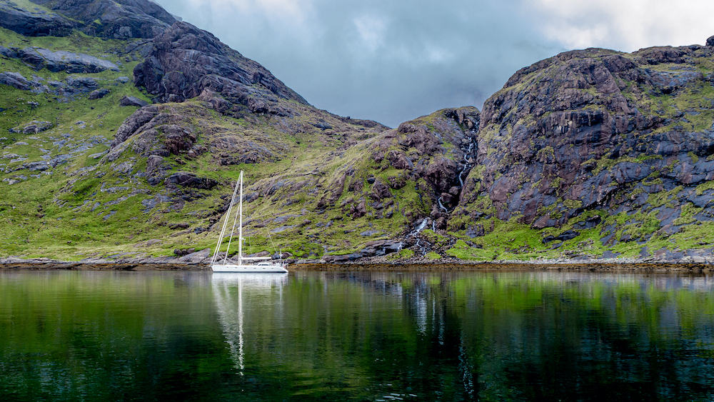 Beautiful view of the loch coruisk at the Isle of Skye with a waterfall in the background and an anchored yacht in the loch, Scotland, United Kingdom