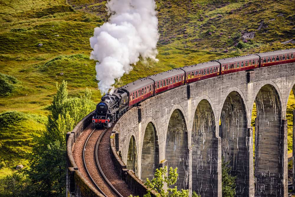 GLENFINNAN, SCOTLAND, UNITED KINGDOM - Glenfinnan Railway Viaduct in Scotland with the Jacobite steam train passing over