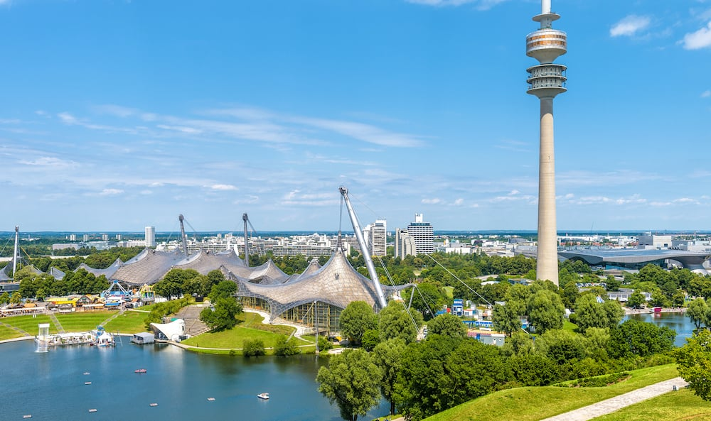 Munich Olympiapark in summer, Germany. It is the Olympic Park, landmark of Munich. Scenic view of former sport area from above. Cityscape of Munich with communication tower. Skyline of Munich city.