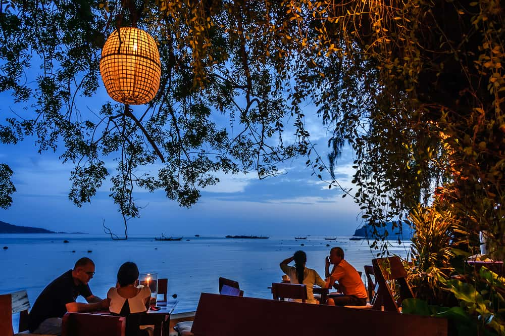 Rawai beach, Phuket, Thailand - Diners sit just after sunset at Nikitas Beach Restaurant on Rawai beach, Phuket, southern Thailand