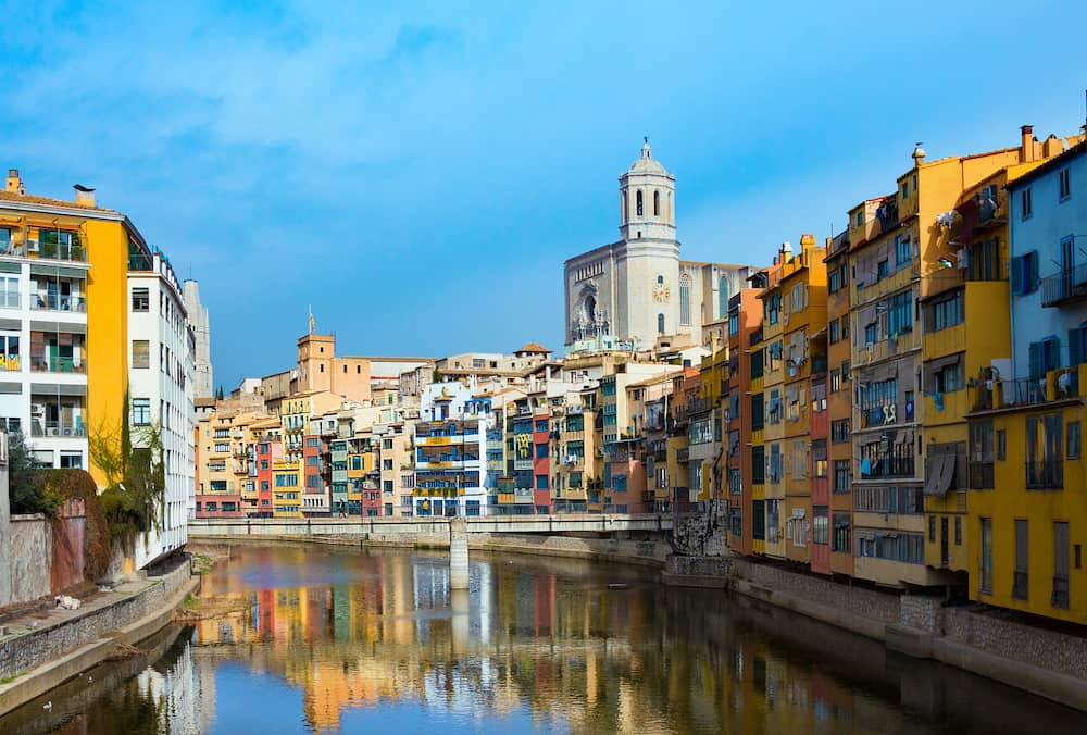 Girona, Spain - Colorful and houses and bridge Pont de Sant Agusti reflected in river Onyar, in Girona, Catalonia, Spain. Saint Mary Cathedral at background in winter