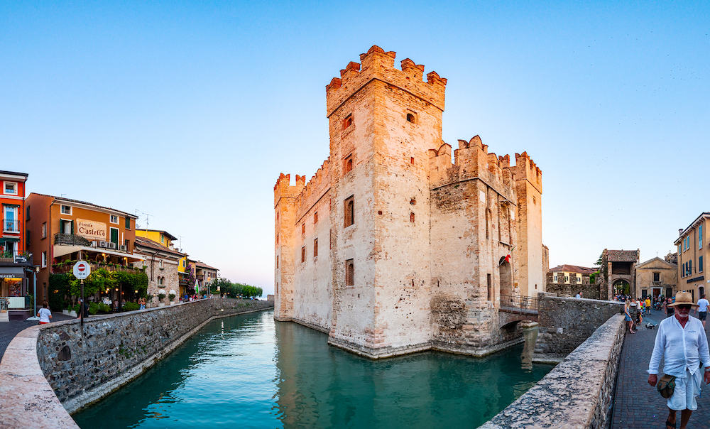 Sirmione, Lombardy, Italy Panorama of Scaligero Castle or Castle of Sirmione surrounded by water canals of the Garda lake. People walking by the streets of the famous Old Town