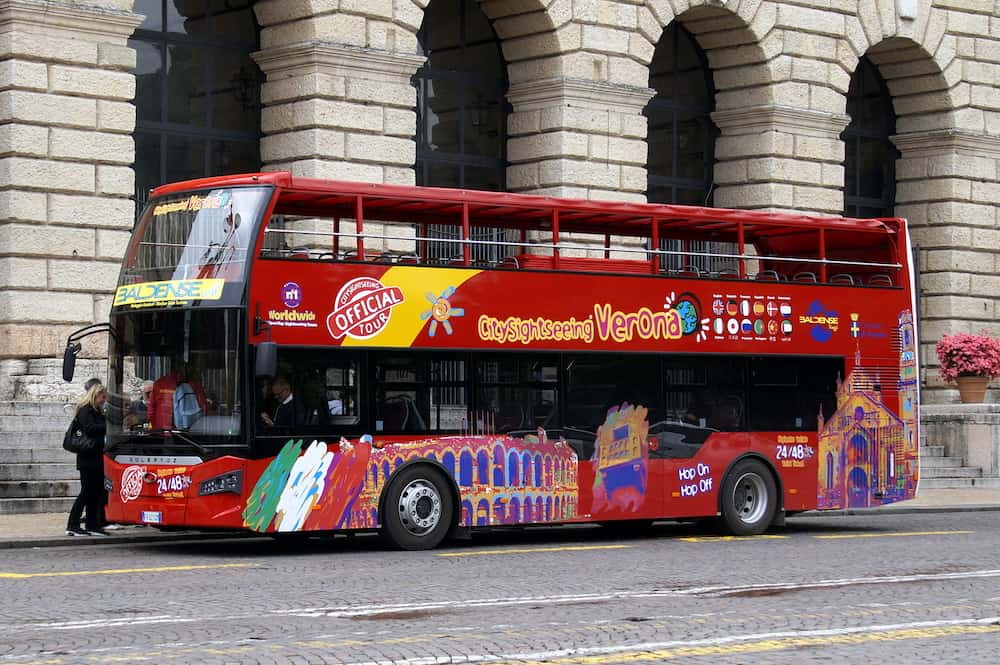Verona, Italy - Unknown and unidentifiable participants entering a Red Güleryüz panorama double decker sightings tourist bus in the city of Verona.