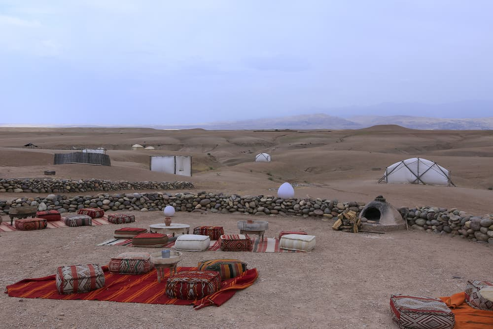 A panoramic view of a glamping site at sunset in the Agafay Desert, near Marrakesh in Morocco