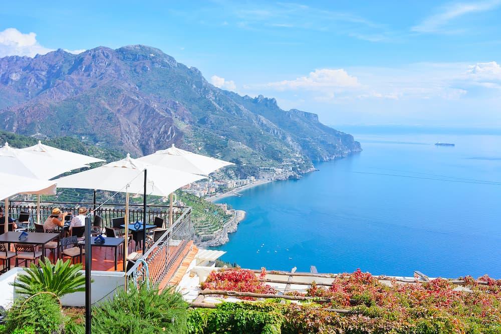 Open air street restaurant with umbrellas in Ravello village Tyrrhenian sea Amalfi coast Italy