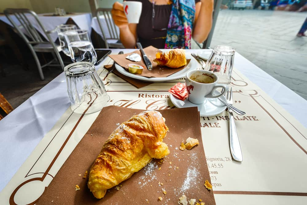 Florence, Italy - A half eaten croissant and breakfast at a sidewalk cafe as a couple enjoy breakfast in the Tuscan city of Florence, Italy