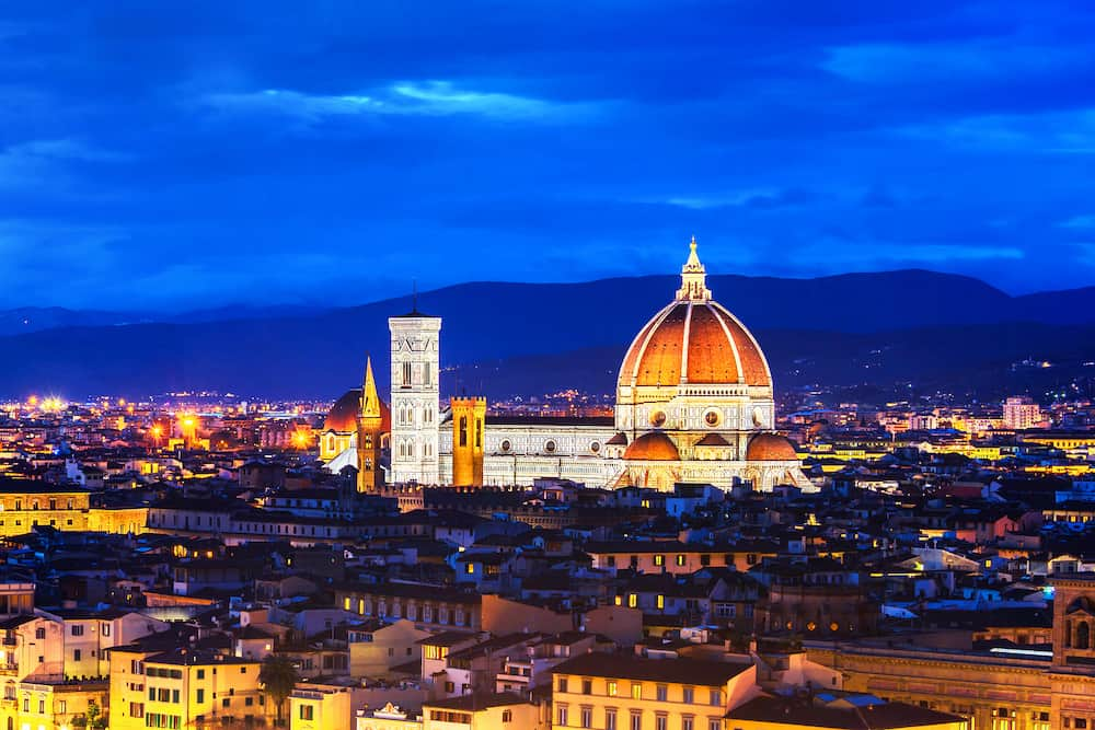 Florence, Italy. Aerial panoramic view of illuminated Florence, Italy at night. Major landmark Cathedral Santa Maria del Fiore and mountains at the background