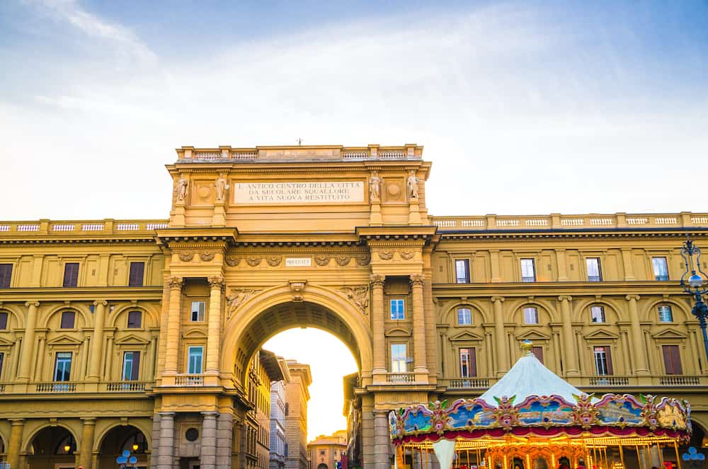 Arch between buildings and Vintage carousel on Piazza della Repubblica Republic square in historical centre of Florence city, blue sky white clouds, Tuscany, Italy