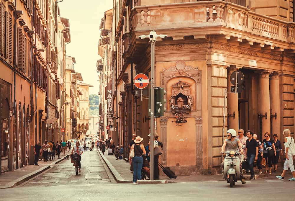 FLORENCE, ITALY - Bike driver and pedestrians on historical streets of ancient Tuscany city on September 25, 2018. Historical Florence is a UNESCO World Heritage Site.