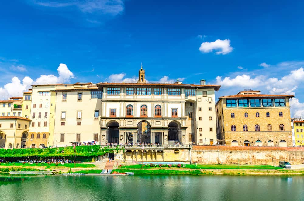Museo Galileo museum, Gallerie degli Uffizi gallery and buildings on embankment promenade of Arno river in historical centre of Florence city, blue sky white clouds background, Tuscany, Italy