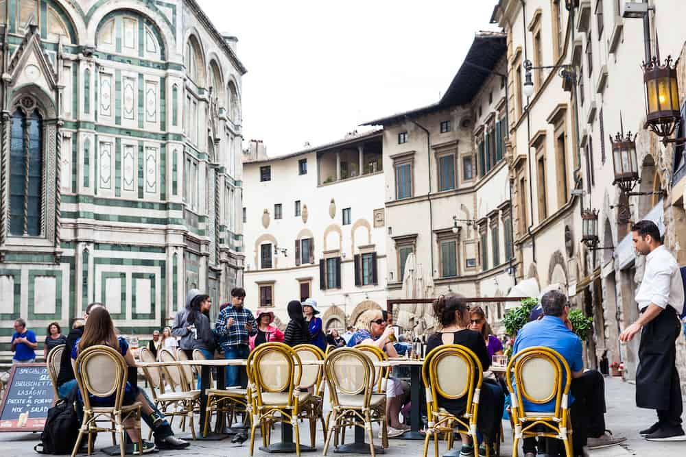 FLORENCE, ITALY - Tourists at a restaurant next to the beautiful Florence Cathedral consecrated in 1436