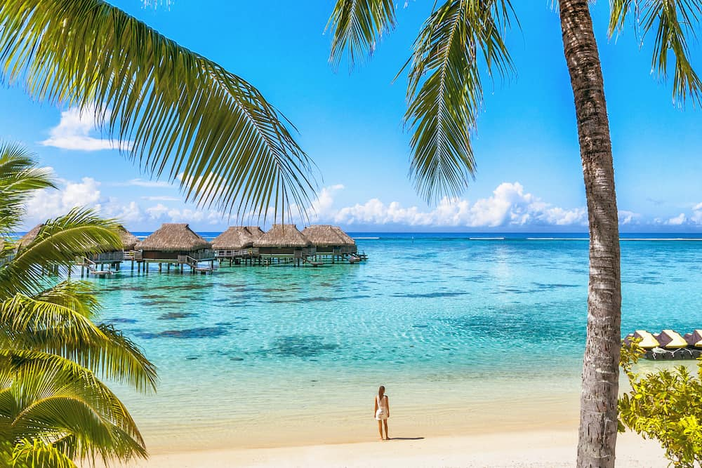 Luxury Tahiti beach resort travel tourist walking on Polynesian beach ocean water at overwater bungalow hotel in French Polynesia, Moorea island in south pacific, famous getaway destination.