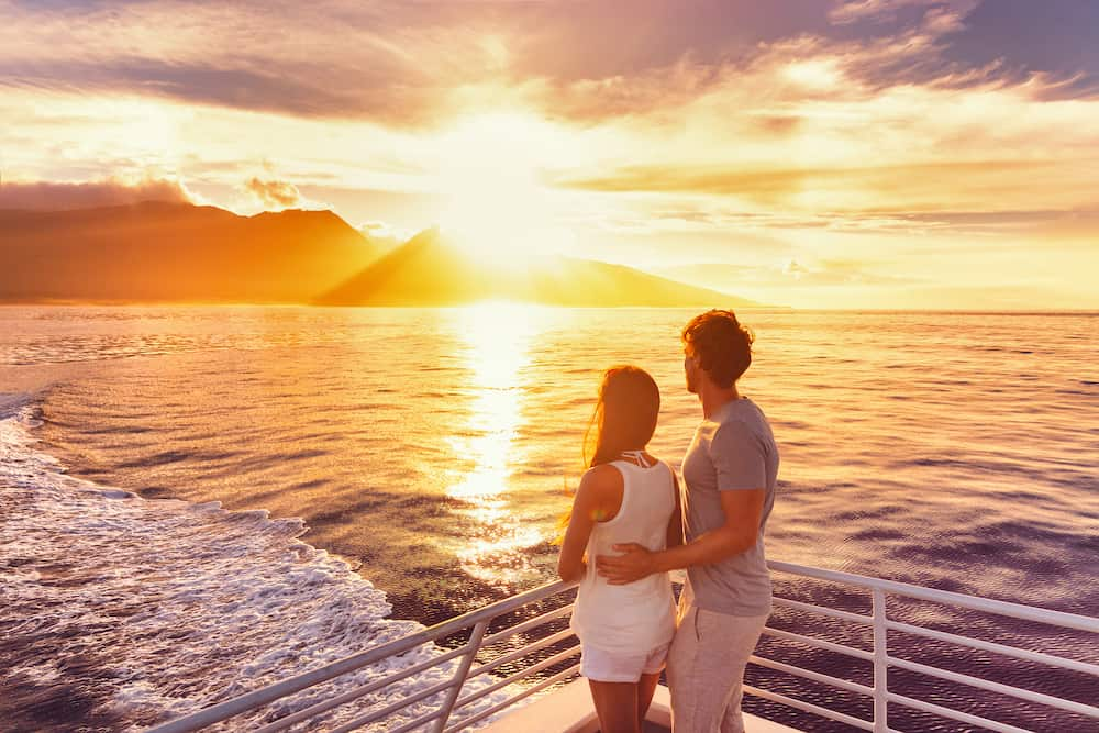 Travel cruise ship couple on sunset cruise on holiday. Two tourists lovers on honeymoon travel enjoying summer vacation.