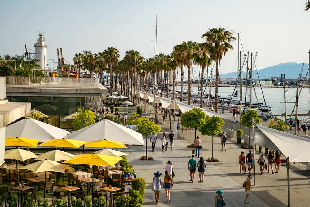 Malaga, Spain - People are walking along the embankment (Paseo Del Muelle Dos Promenade) which stretches through port under a construction resembeling white wave in Malaga, Spain.
