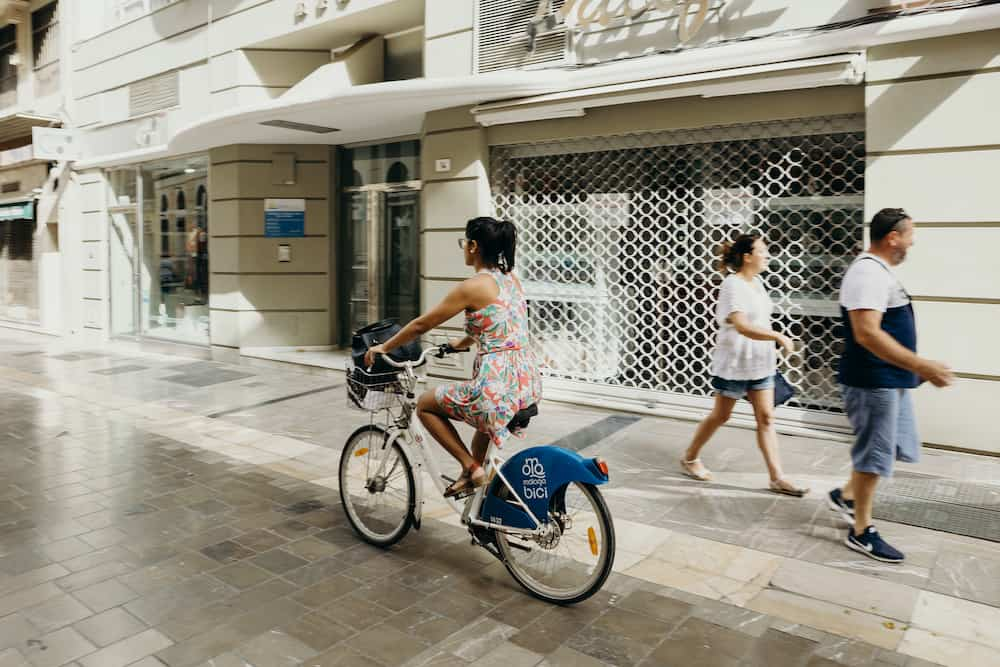 MALAGA, SPAIN - Woman riding a bicycle during a journey in the city center of Malaga, Spain.