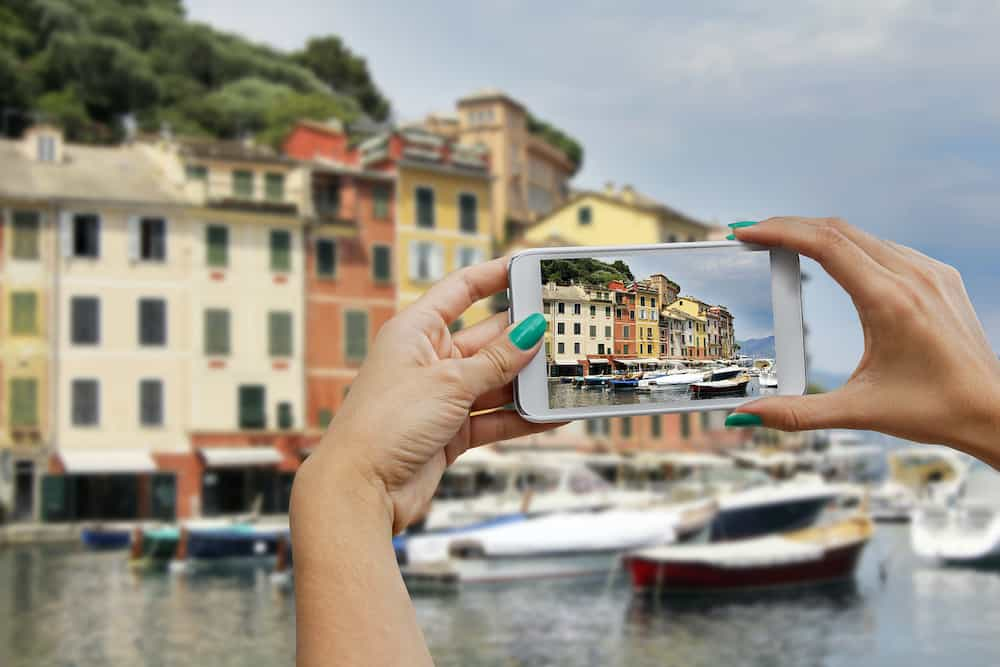 A woman photographing with mobile phone Portofino Cinque Terre Italy