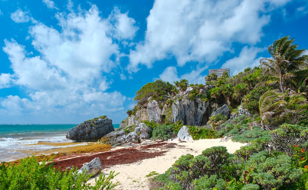 Tropical beach and ancient mayan ruins on a cliff at Tulum in the Mayan Riviera, Mexico