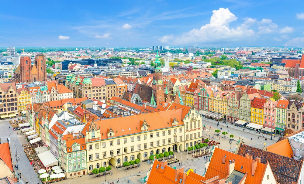 Top aerial panoramic view of Wroclaw old town historical city centre with Rynek Market Square, Old Town Hall, New City Hall, colorful buildings with multicolored facade and tiled roofs, Poland