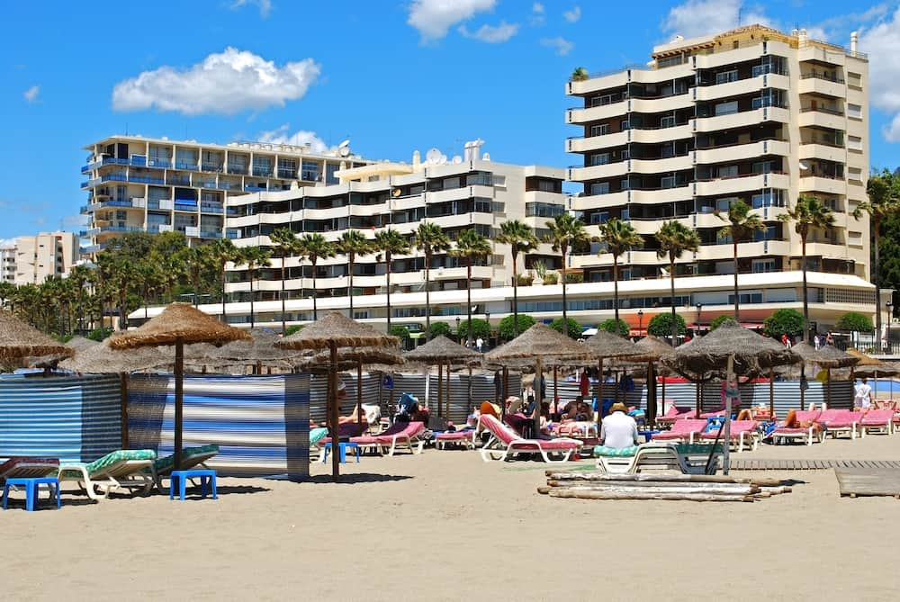 MARBELLA, SPAIN - Tourists relaxing on Daitona beach with hotels and apartments to the rear, Marbella, Malaga Province, Andalucia, Spain, Western Europe