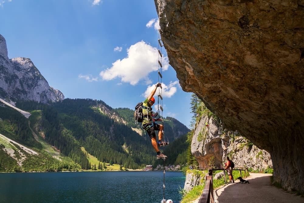 GOSAU, AUSTRIA - : Man climbing on Laserer alpin via ferrata over Vorderer Gosausee lake with Grosser Donnerkogel Mountain in background in Gosau, Austria.