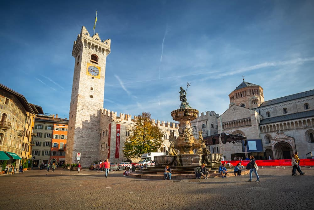Trento, Italy - People walking at the fountain of Neptune on Piazza Duomo in Trento, South Tyrol. Italy