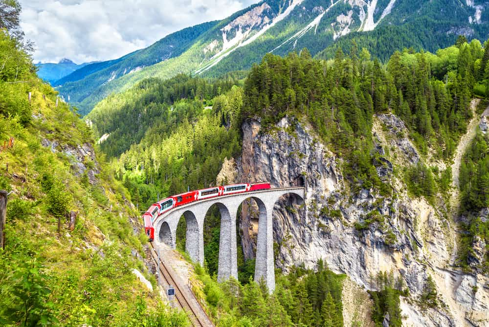 Landwasser Viaduct in summer, Filisur, Switzerland. It is landmark of Swiss Alps. Nice Alpine landscape. Red train of Bernina Express on railroad bridge in mountains. Panoramic view of famous railway.